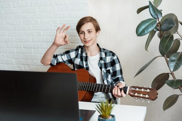 Młody przystojny nastolatek chłopiec uczy się gry na gitarze klasycznej z lekcji online uśmiechnięty szczęśliwy robi ok znak ręką