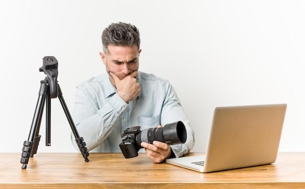 Młody przystojny nauczyciel fotografii patrzy w bok z wątpliwym i sceptycznym wyrazem twarzy.