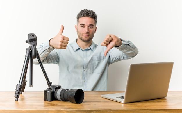Młody przystojny nauczyciel fotografii pokazujący kciuki do góry i kciuki w dół, trudny wybór