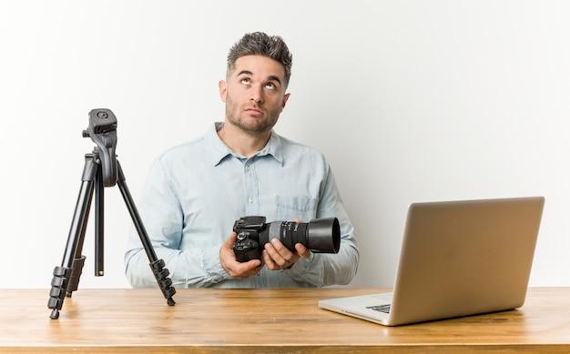Młody przystojny nauczyciel fotografii zmęczony powtarzalnym zadaniem.