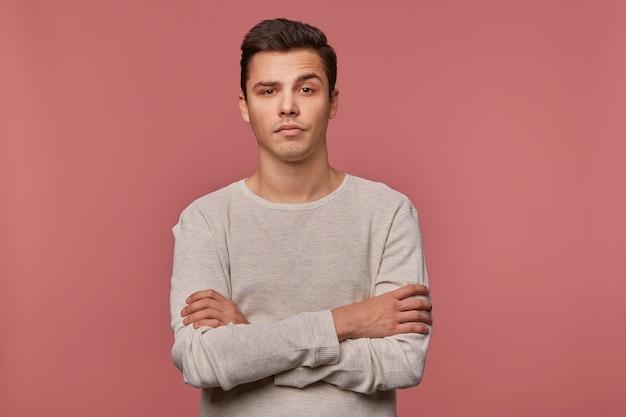 Młody przystojny niezadowolony facet nosi w kraciastej koszuli, patrzy w kamerę z obrzydzonym wyrazem, zgniecione ramiona, odizolowane na różowym tle.