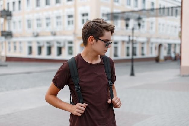 Młody przystojny nowoczesny hipster mężczyzna w ciemnych stylowych okularach przeciwsłonecznych w modnych letnich ubraniach z plecakiem spaceruje po mieście w letni dzień