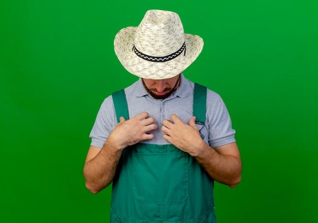 Młody przystojny ogrodnik słowiański w mundurze i kapeluszu dotykając klatki piersiowej i patrząc na nią