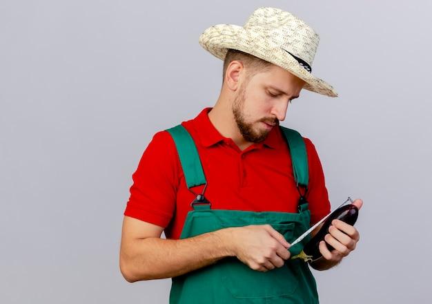 Młody przystojny ogrodnik słowiański w mundurze i kapeluszu trzyma bakłażana i mierzy go z miernikiem taśmy na białym tle