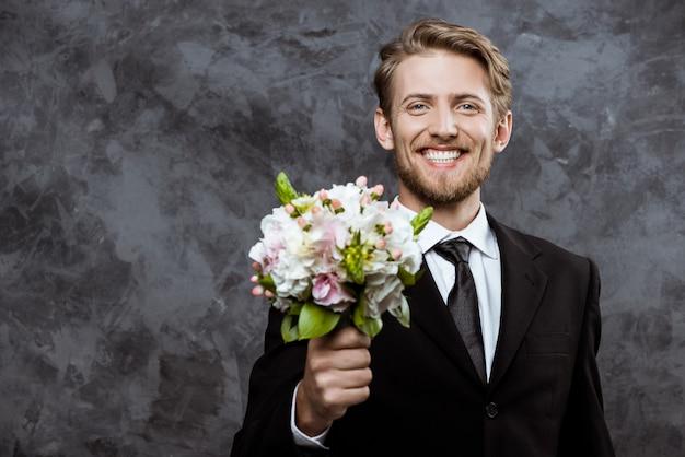 Młody przystojny pan młody uśmiecha się, trzymając bukiet ślubny
