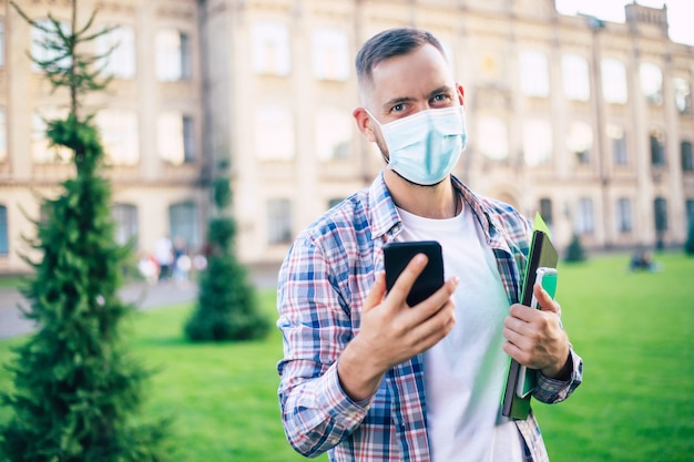 Młody przystojny pewnie student mężczyzna w masce medycznej patrzy w kamerę i stoi przy uniwersytecie