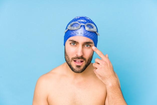 Młody przystojny pływak mężczyzna na białym tle pokazując gest rozczarowania z palcem wskazującym.