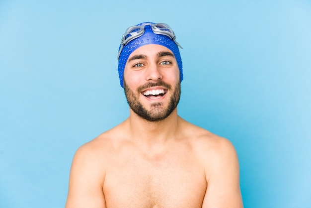Młody przystojny pływak mężczyzna na białym tle śmiejąc się i zabawy.