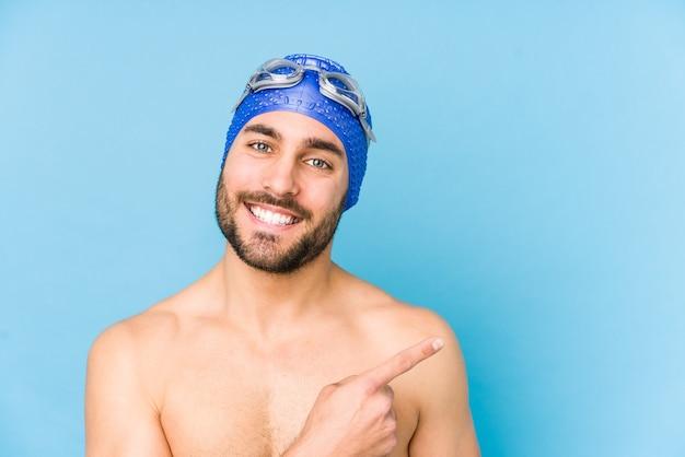 Młody przystojny pływak mężczyzna na białym tle, uśmiechając się i wskazując na bok, pokazując coś w pustej przestrzeni.