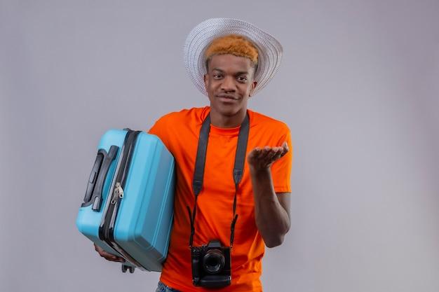 Młody przystojny podróżnik chłopiec w letnim kapeluszu na sobie pomarańczową koszulkę z aparatem trzymając walizkę podróżną