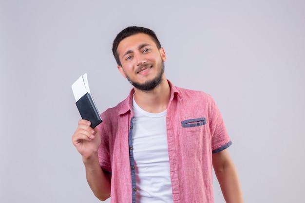 Młody przystojny podróżnik facet bilety lotnicze patrząc na kamery z pewnym uśmiechem na twarzy szczęśliwa i pozytywna pozycja na białym tle