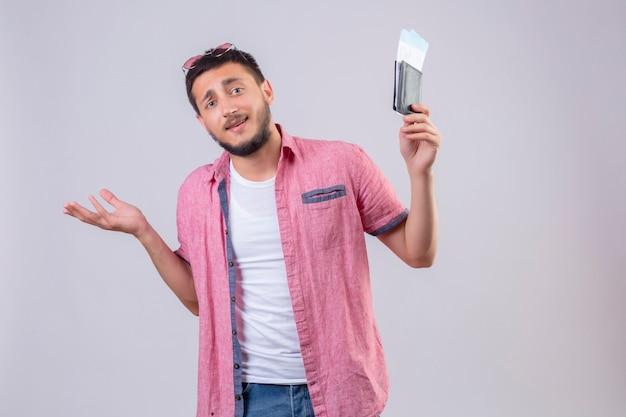 Młody przystojny podróżnik facet posiadający bilety lotnicze nieświadomy i zdezorientowany stojąc z podniesionymi rękami bez odpowiedzi na białym tle