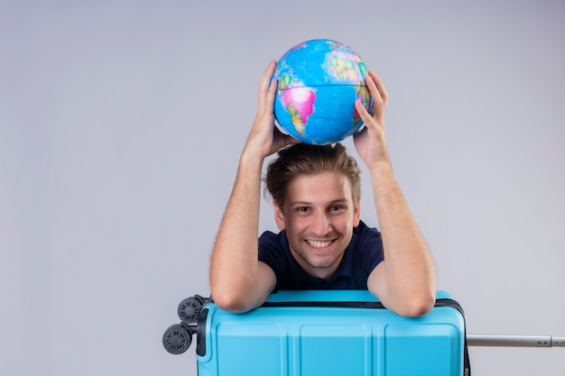 Młody przystojny podróżnik facet stojący z walizką trzymając kulę ziemską patrząc na kamery, uśmiechając się radośnie z szczęśliwą twarzą na białym tle