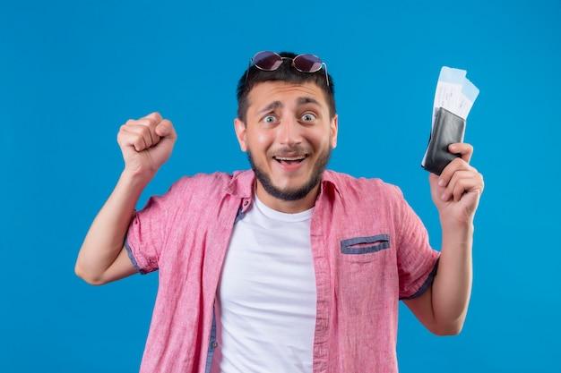 Młody przystojny podróżnik facet trzyma bilety lotnicze patrząc podekscytowany i szczęśliwy, podnosząc pięść stojącą na niebieskim tle