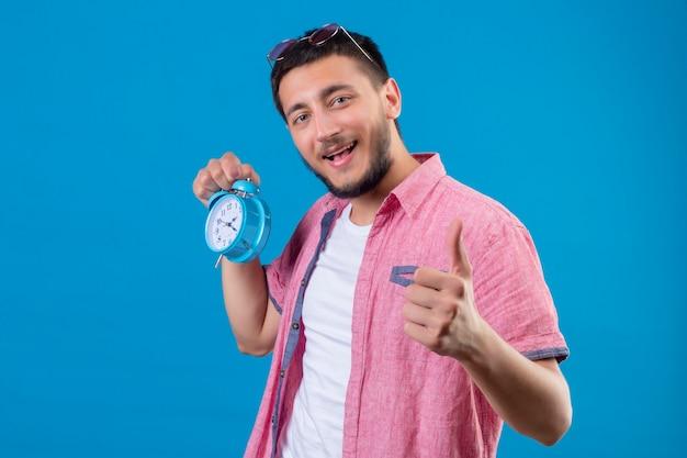 Młody przystojny podróżnik facet trzyma budzik patrząc pozytywnie i szczęśliwie uśmiechając się pokazując kciuki stojąc na niebieskim tle