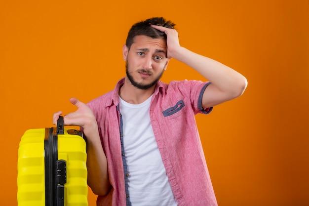 Młody przystojny podróżnik facet trzyma walizkę stojącą z ręką na głowie za błąd pamięta błąd złą koncepcję pamięci na pomarańczowym tle