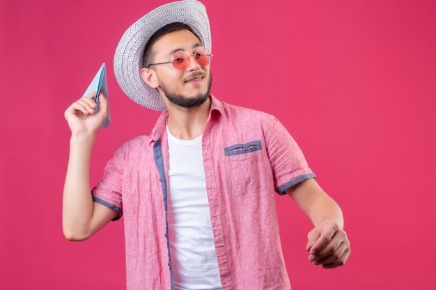 Młody przystojny podróżnik facet w letnim kapeluszu w okularach przeciwsłonecznych patrząc pewnie rzucający papierowy samolot stojący na różowym tle