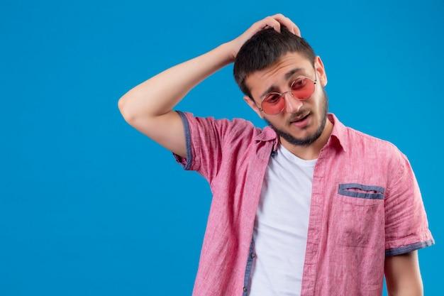 Młody przystojny podróżnik facet w okularach przeciwsłonecznych stojących z ręką na głowie za błąd pamiętaj o błędzie złej koncepcji pamięci stojącej na niebieskim tle