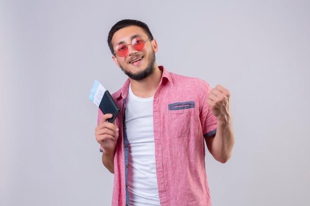 Młody przystojny podróżnik facet w okularach przeciwsłonecznych, trzymając bilety lotnicze, patrząc na kamerę, wyszedł i szczęśliwy, podnosząc pięść po koncepcji zwycięzcy zwycięstwa stojącej na białym tle