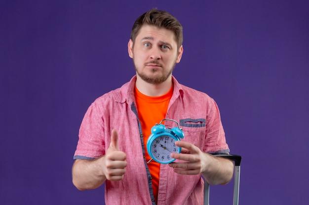 Młody przystojny podróżnik mężczyzna trzyma niebieską walizkę i budzik pokazując kciuki ze smutnym wyrazem twarzy