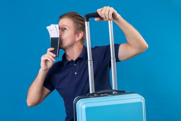 Młody przystojny podróżnik mężczyzna trzyma walizkę i całuje bilety w ręku patrząc szczęśliwy stojący na niebieskim tle