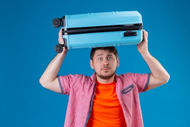 Młody przystojny podróżnik mężczyzna trzyma walizkę na głowie emocjonalny i zmartwiony wyrazem strachu na twarzy stojącej nad niebieską ścianą