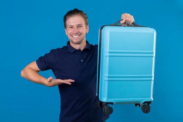 Młody przystojny podróżnik mężczyzna trzyma walizkę patrząc pewnie przedstawia z ręką jego walizkę uśmiechając się wesoło stojąc na niebieskim tle