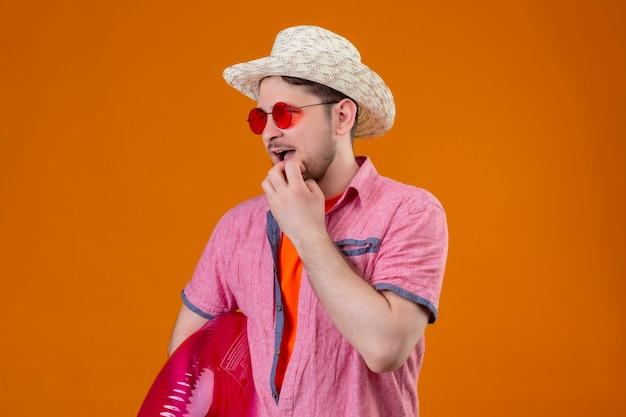 Młody przystojny podróżnik mężczyzna w kapeluszu lato z nadmuchiwanym pierścieniem patrząc na bok