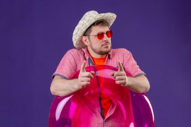 Młody przystojny podróżnik mężczyzna w kapeluszu lato z nadmuchiwanym pierścieniem wskazującym palcami