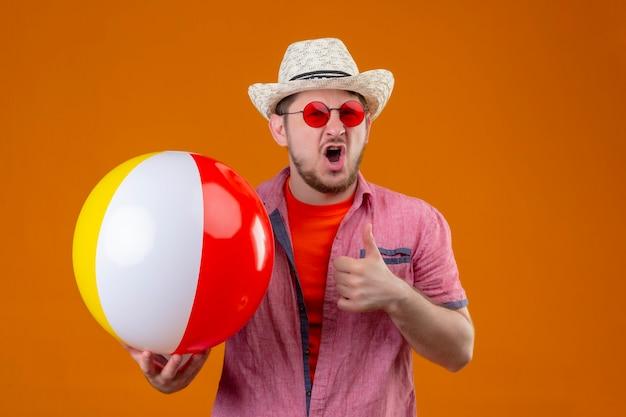Młody przystojny podróżnik mężczyzna w letnim kapeluszu, trzymając nadmuchiwaną piłkę