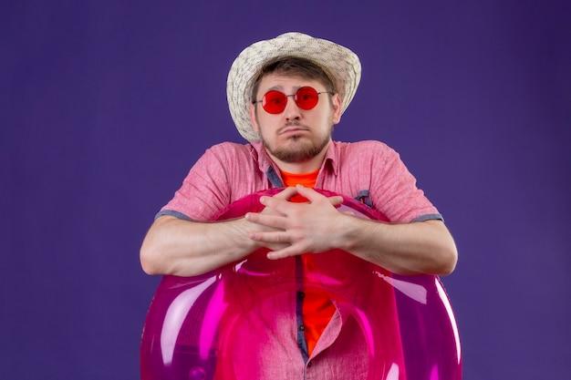 Młody przystojny podróżnik mężczyzna w letnim kapeluszu z nadmuchiwanym pierścieniem mylić ze smutnym wyrazem twarzy