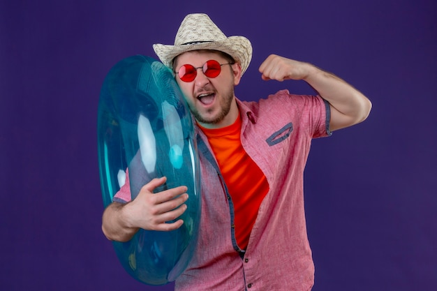 Młody przystojny podróżnik mężczyzna w letnim kapeluszu z nadmuchiwanym pierścieniem podnoszącym pięść