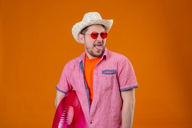 Młody przystojny podróżnik mężczyzna w letnim kapeluszu z nadmuchiwanym pierścieniem, wystawiający język z obrzydzonym wyrazem twarzy