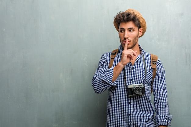 Młody przystojny podróżnik w słomkowym kapeluszu, plecaku i aparacie fotograficznym utrzymującym w tajemnicy lub proszącym o ciszę, poważną twarz, posłuszeństwo