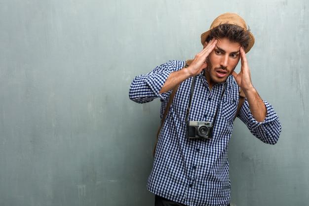 Młody przystojny podróżnika mężczyzna jest ubranym słomianego kapelusz, plecaka i fotografii kamerę udaremniającą, desperacką, gniewną i smutną z rękami na głowie