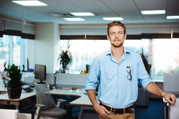 Młody przystojny pomyślny biznesmen ono uśmiecha się, pozuje, nad biurem