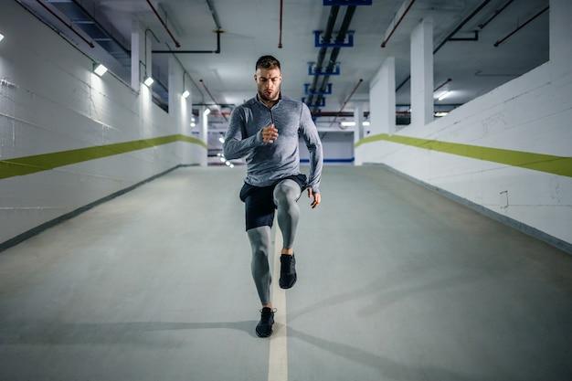 Młody przystojny, potężny, muskularny sportowiec kaukaski w aktywnym ubraniu biegający w podziemnym garażu w nocy. koncepcja życia miejskiego.