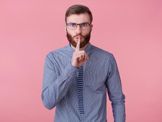Młody przystojny rudy brodaty mężczyzna w okularach i koszuli w paski, trzyma palec na ustach, mówi tajne informacje, demonstruje gest ciszy na różowym tle.