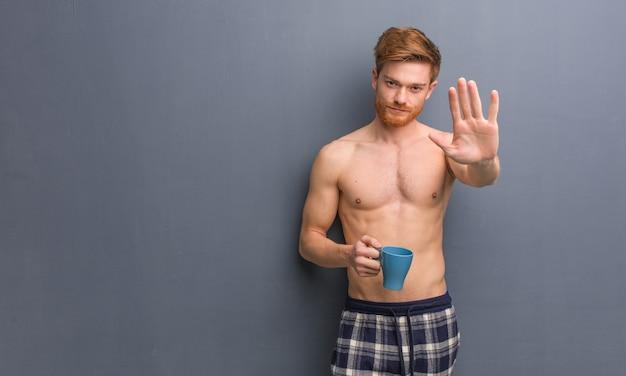 Młody przystojny rudy mężczyzna kładzie rękę z przodu. trzyma kubek kawy.