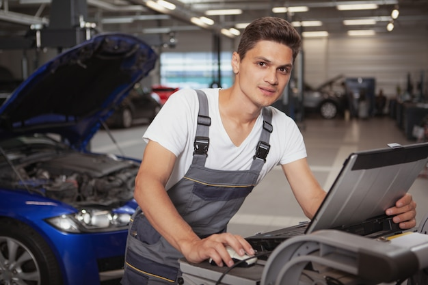 Młody przystojny samochodowy mechanik naprawia pojazd w jego garażu