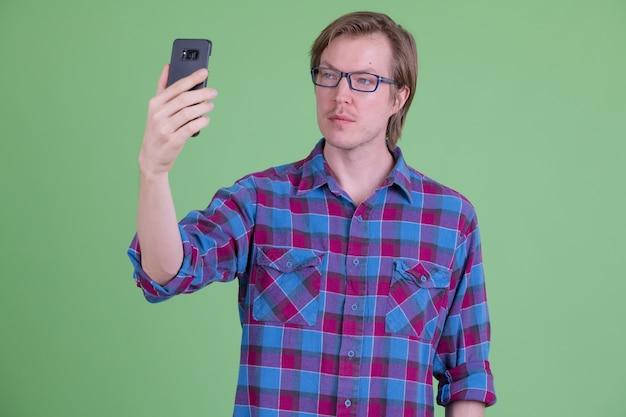 Młody przystojny skandynawski hipster mężczyzna w okularach przeciwko klucz chrominancji z zielonym tłem