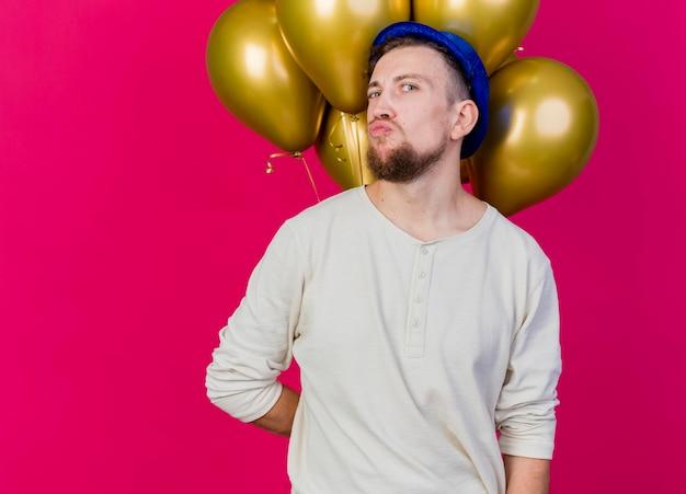 Młody przystojny słowiański imprezowicz w kapeluszu imprezowym, trzymając balony za plecami, patrząc z przodu, robi gest pocałunku na różowej ścianie z miejsca na kopię