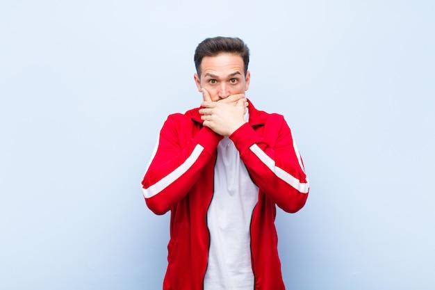 Młody przystojny sportowiec lub monitor zakrywający usta dłońmi z zszokowanym, zdziwionym wyrazem, zachowujący tajemnicę lub mówiąc: ups o ścianę