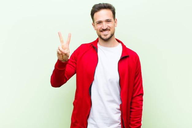 Młody przystojny sportowiec mężczyzna lub monitor uśmiechnięty i wyglądający przyjazny, pokazując numer dwa lub drugi ręką do przodu, odliczając w dół na płaskiej ścianie