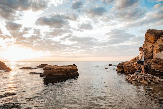 Młody przystojny sportowiec stojący na kamienistej plaży nad morzem