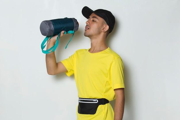 Młody przystojny sportowiec wody pitnej po treningu na białym tle