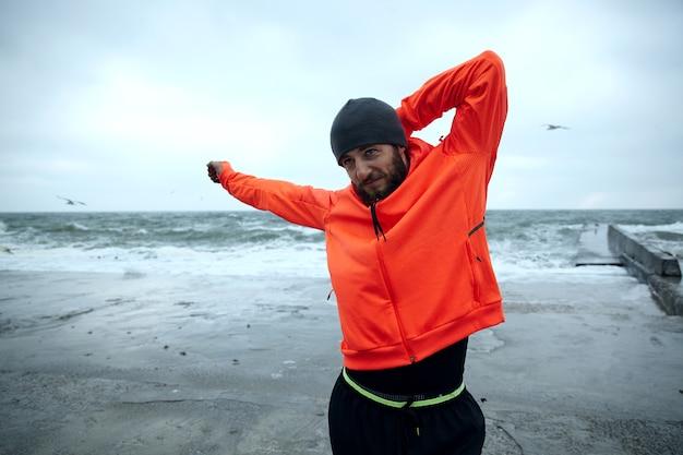 Młody przystojny, sportowy, ciemnowłosy, brodaty mężczyzna robi ćwiczenia rozciągające na świeżym powietrzu, przygotowując się do porannego treningu, ubrany w czarne ciepłe sportowe ubrania i pomarańczowy płaszcz z kapturem