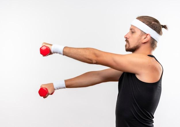 Młody przystojny sportowy mężczyzna ubrany w opaskę i opaski na rękę trzymając hantle i wyciągając ręce stojąc w widoku profilu patrząc na bok na białym tle na białej przestrzeni