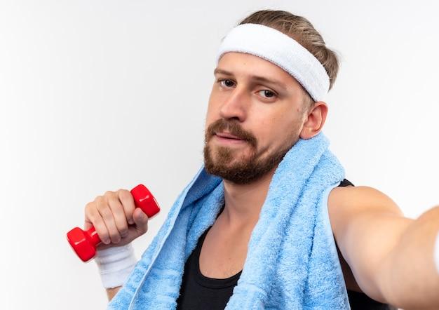 Młody przystojny sportowy mężczyzna z opaską na głowę i opaskami na rękę trzymający hantle z ręcznikiem na szyi wyciągający rękę w kierunku i patrząc odizolowany na białej przestrzeni
