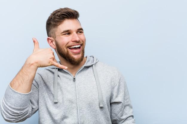 Młody przystojny sprawność fizyczna mężczyzna pokazuje telefonu komórkowego wezwania gest z palcami.